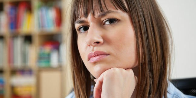 Sceptical woman wears an incredulous expression, scrunches eyes