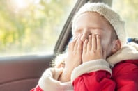Young girl feeling bored in passenger seat of car