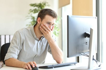 Man holds hand over mouth as he looks at monitor in a worried manner