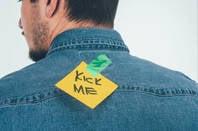 kick me sign on man's back