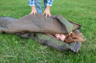 Two people sleeping in a meadow to raise charity