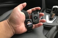 Man holds the BMW f30 key fob with an apple watch showing the connected drive information.