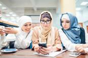 Three women looking at their phones