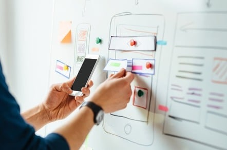Person holding smartphone during whiteboard web design session