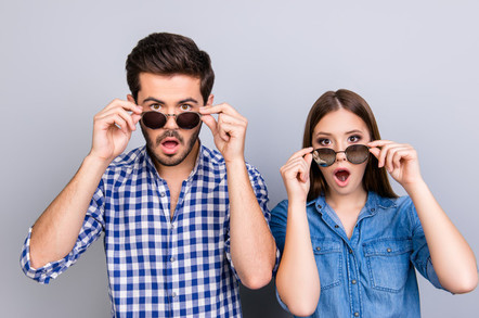 Couple wearing sunglasses looking surprised by something