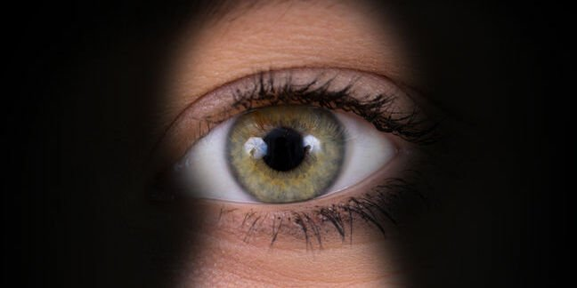 Green eye peeking through keyhole