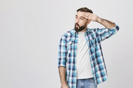 man mops sweat from brow in relieved way/ relief