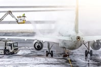 Ground crew de-icing aircraft