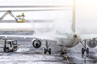 Ground crew de-icing aircraft