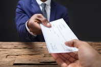 Man handing another person a paycheck