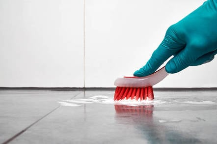 A male hand scrubs a floor