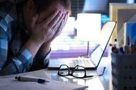 man in front of laptop puts head in hands - despairing