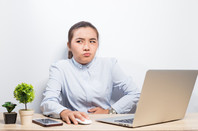 Woman looks sceptical at laptop