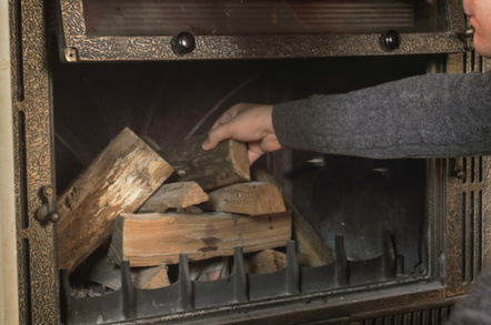 Man stacks  pre-cut wood in a fireplace
