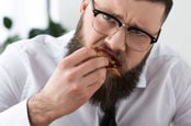 man in tie eats slice of pizza, looks sad while doing so