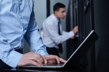 Man furtively types on laptop in server room