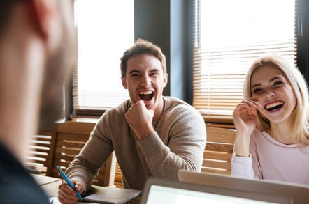 laughing colleagues in front of laptops