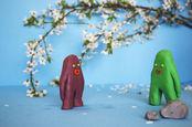 Two plasticine blobs against a garden landscape