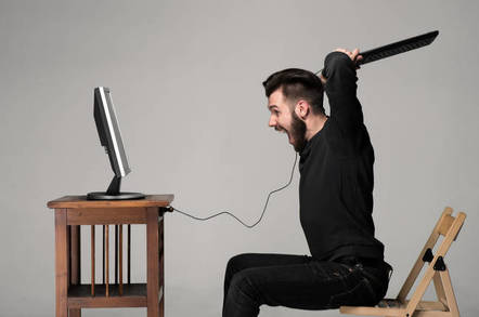 Angry man wields keyboard at a computer
