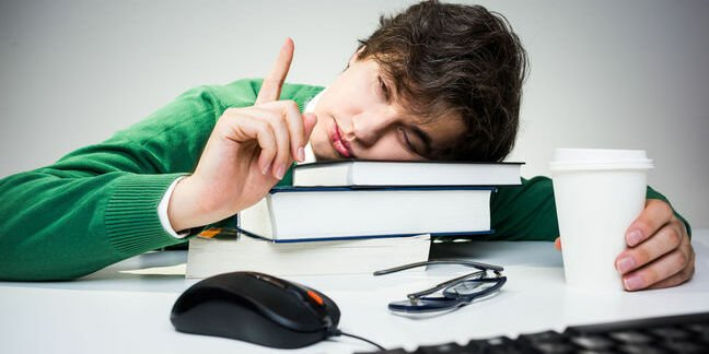 staffer props head on pile of books as he clicks a mouse and fights sleep