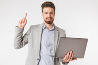 Man holding laptop computer and pointing finger up