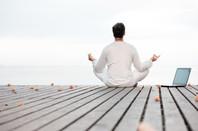 man meditating next to a laptop