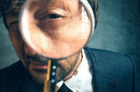 man holds magnifying glass