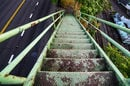 rusted stairs descend onto footpath between highway and train track