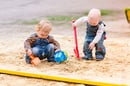 Two baby boys playing with sand in a sandbox
