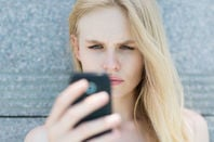 woman thinks intently as she uses smartphone