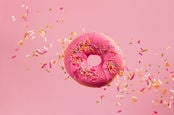 Iced pink doughnut flies through the air as it is showered with sprinkles