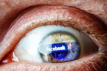 panicked eye with Facebook logo reflected on surface