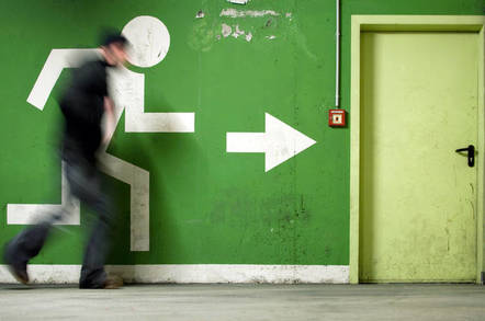 Man runs to fire exit in a corridor
