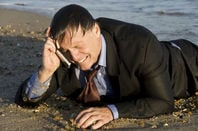 crying business man washed up on beach talks into phone