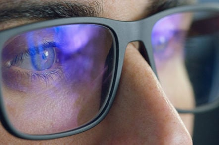 Man looks at computer screen which is reflected in his glasses