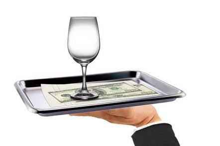 A wine glass and some money on a silver platter