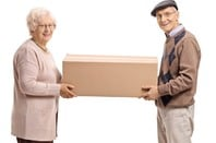 Elderly woman and man holding a cardboard container