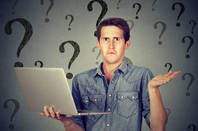 A man shrugs at a laptop with a background of question marks