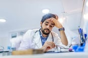 annoyed doctor tired at computer