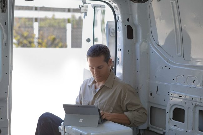 Man in white van using a Surface Go