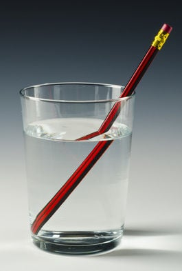 A straw in a glass of water shows how light refracts differently in the liquid. Pic: Shutterstock/Pat Hastings