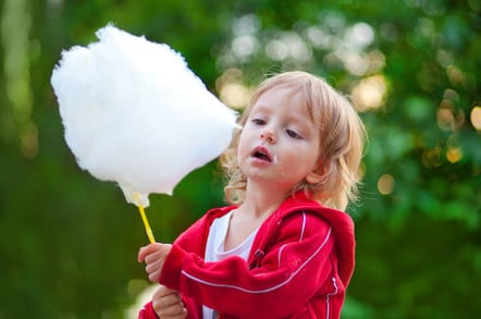 Little girl eating cotton candy in the park