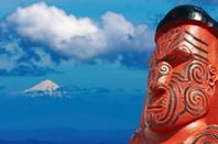 Traditional maori carving over Taranaki Mount background, New Zealand.