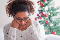 woman looks pensive in front of a christmas tree
