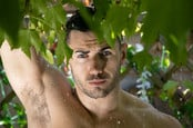Shirtless man under rain shower in garden