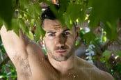 Shirtless man in the rain shower in the garden