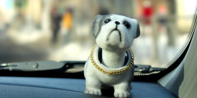 A nodding toy dog on the dashboard of a car