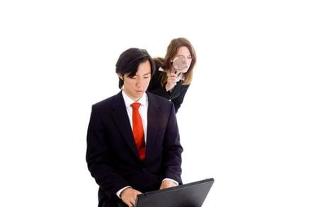A woman looking over a man's shoulder at his computer screen