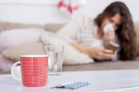 woman surrounded by piles of tissues uses smartphone app