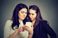 two women look disgusted at what they see on a phone screen